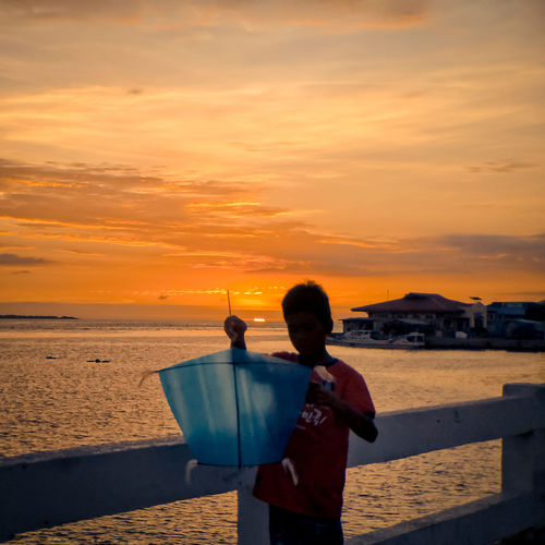 A child tries to fly a kite during sunset at Rio Hondo Mobilephotography Mobile Photography Golden Hour Silhouette Street Photography Streetphotography EyeEm Best Shots Philippines Zamboanga City Zamboanga Kite Kite Flying Street Street Scene Child Sea Sunset Beach Water Standing Beauty Sun Romantic Sky Dramatic Sky The Mobile Photographer - 2019 EyeEm Awards The Street Photographer - 2019 EyeEm Awards My Best Photo The Great Outdoors - 2019 EyeEm Awards