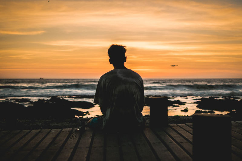 Rear View Of A Man Sitting On Shore During Sunset