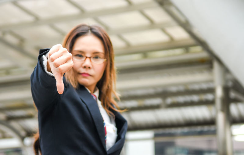 Close-up of businesswoman showing thumbs down while standing outdoors