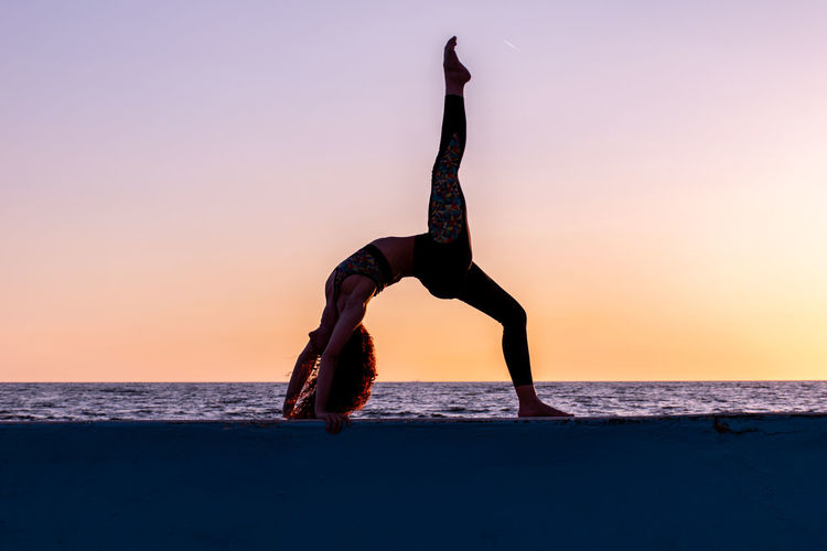 Full length of woman practicing yoga by sea against sky during sunset