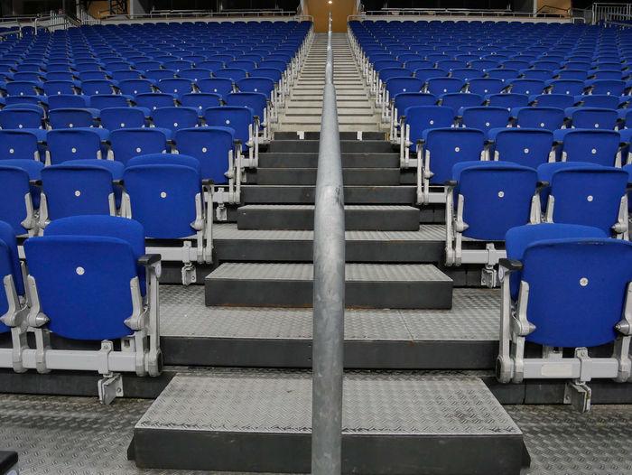 Empty blue chairs at stadium