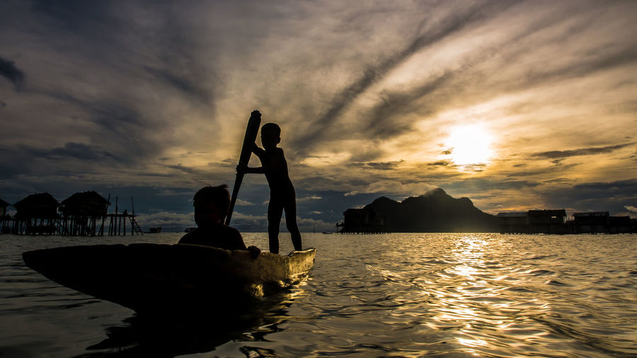 Silhouette Children Rowing Boat In River During Sunset