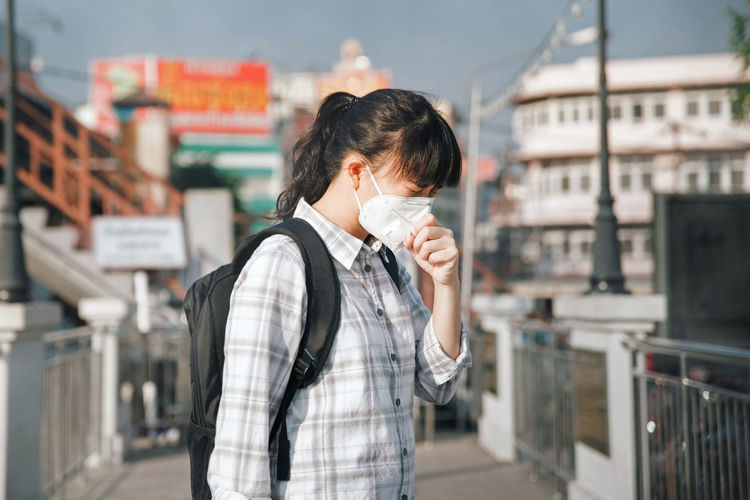 Woman wearing pollution mask while standing on footpath