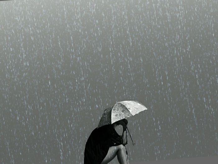 Woman with umbrella sitting outdoors during rainy season
