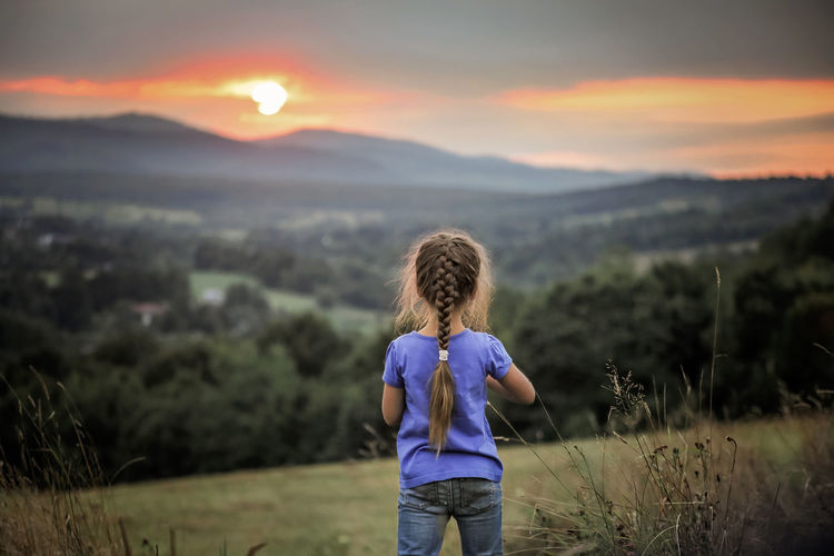 Rear view of boy standing on field during sunset