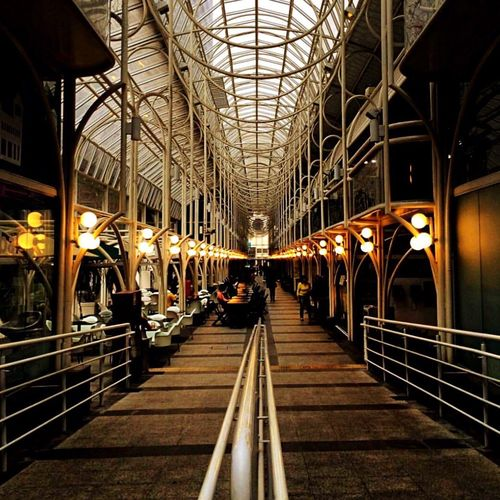 Illuminated Indoors  Architecture Transportation Built Structure The Way Forward Railing Ceiling Railroad Station Diminishing Perspective Modern Group Of People City Life Arch Person Long Narrow Retail  First Eyeem Photo