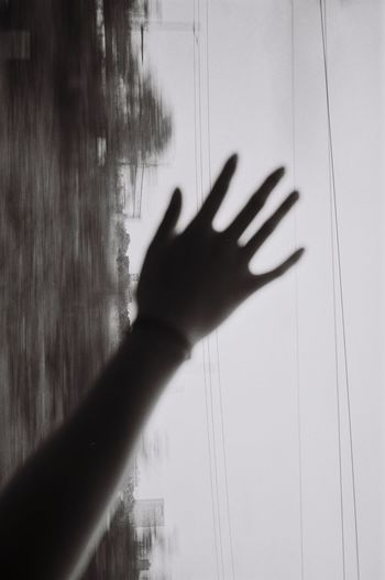 Shadow of person hand on glass window