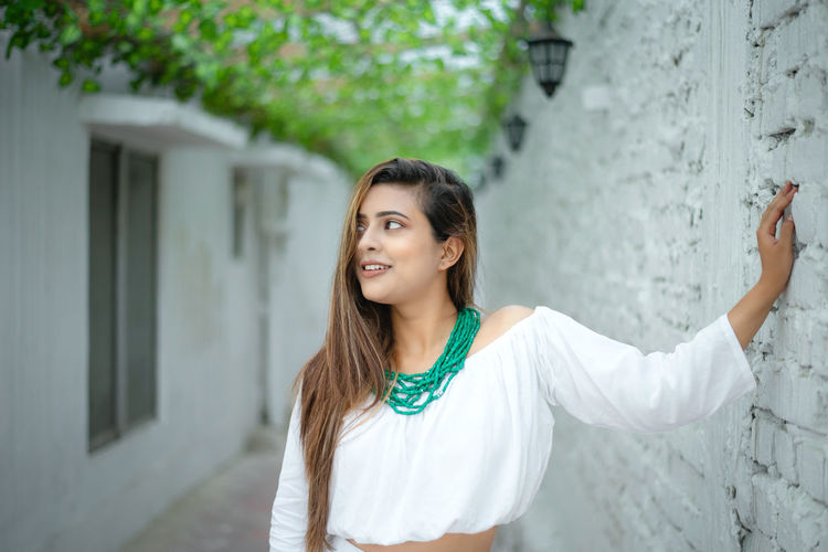 Beautiful young woman standing against wall
