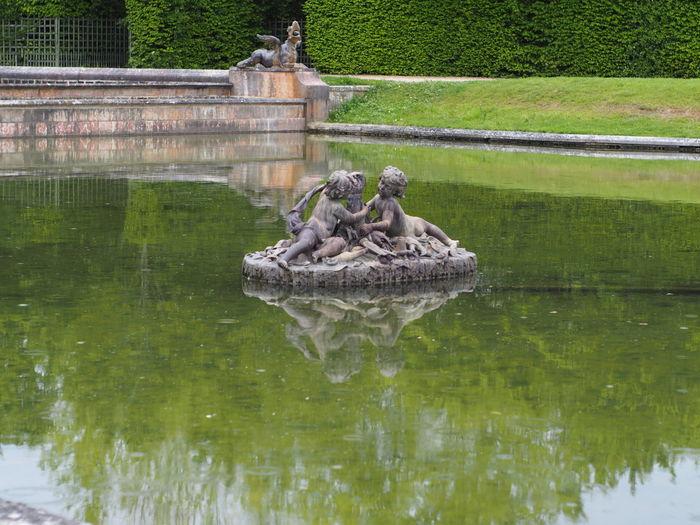 Statue on lake against trees