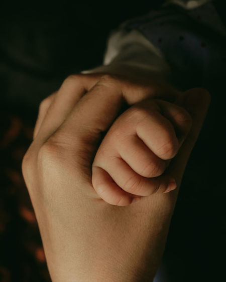 Close-up of mother holding hands