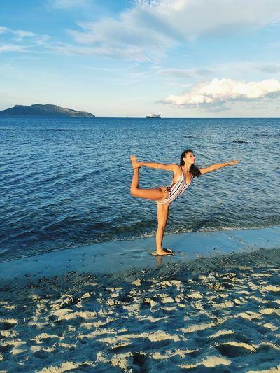 Gymnast standing on beach by sea against sky