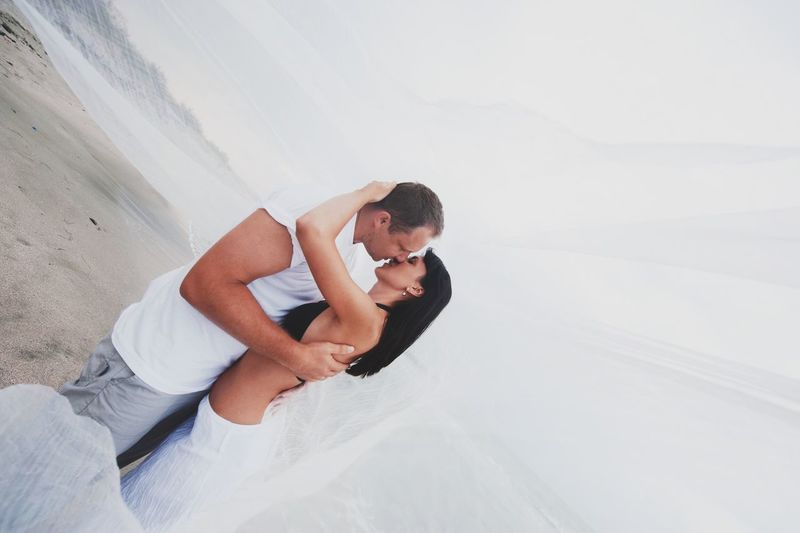 Couple kissing amidst white fabric