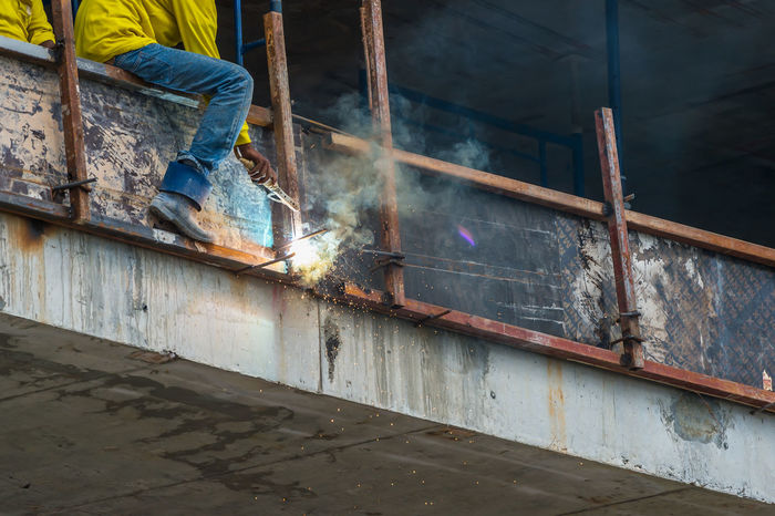 Worker are welding steel at construction site. Construction Site Day Indoors  Industry Low Section Manual Worker Men Metal Industry Motion Occupation One Person People Protective Workwear Real People Reflective Clothing Welder Welding Welding Work Working