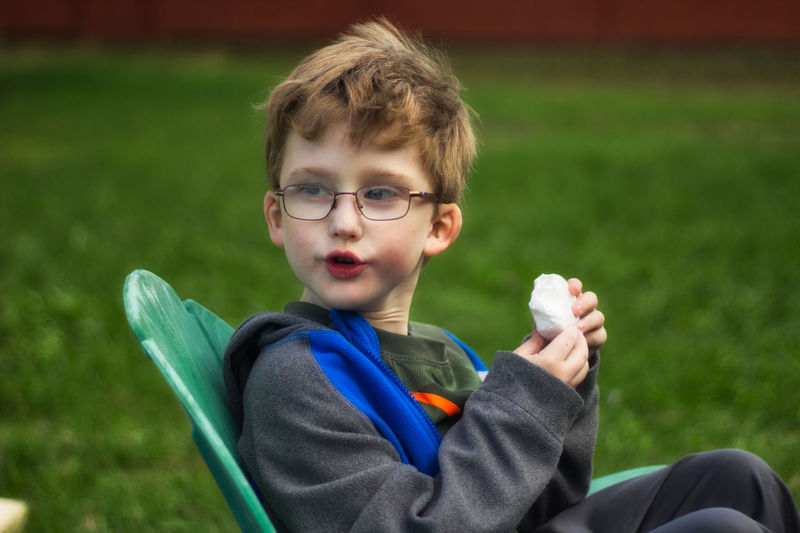 Boy holding food while sitting on chair over grass