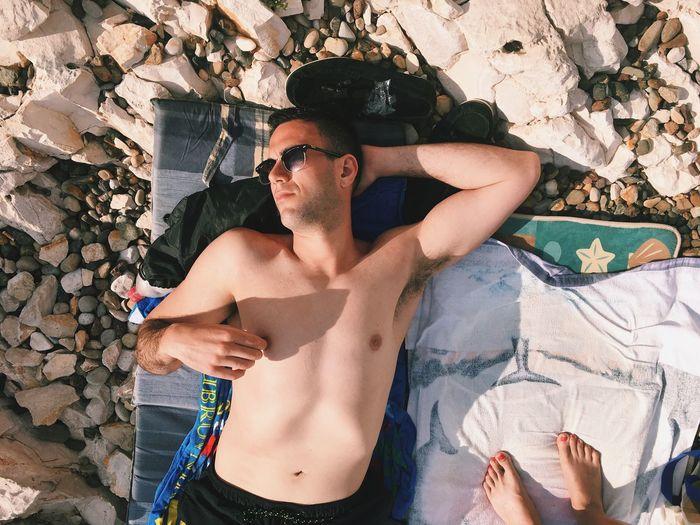 Portrait of man sunbathing on beach