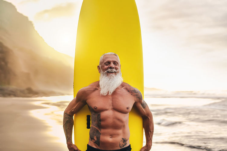 Portrait of shirtless man holding surfboard against sea