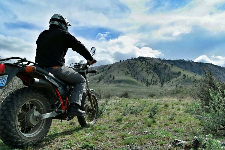 Man riding motorcycle towards mountain against sky
