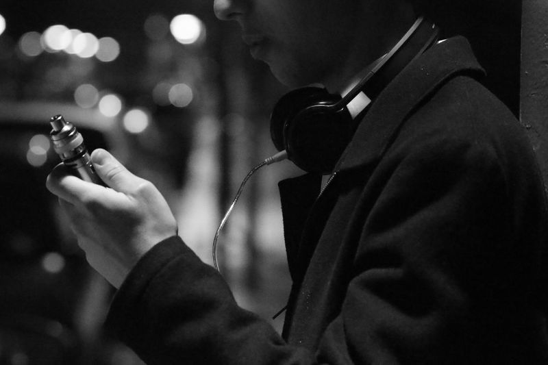 A guy with an electronic cigarette at night on the street Evening Night Blackandwhite Street Light Guy Adult Unhealthy Human Hand Men Holding Close-up Smoking Bad Habit Cigarette  Smoking - Activity Blues Music Unhealthy Living