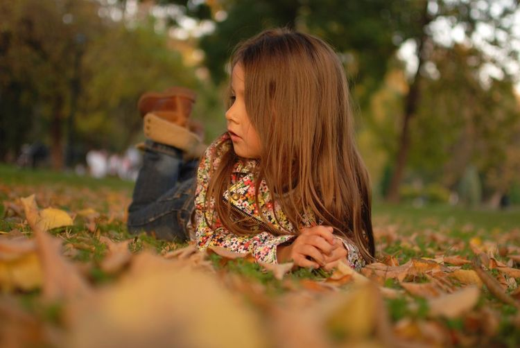 Thoughtful girl resting on field in park during autumn