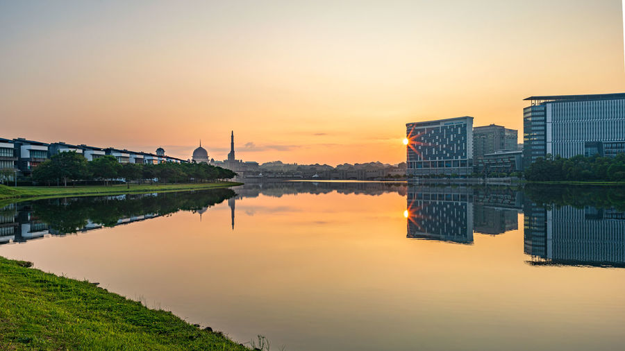 Reflection of buildings in lake against sky during sunset
