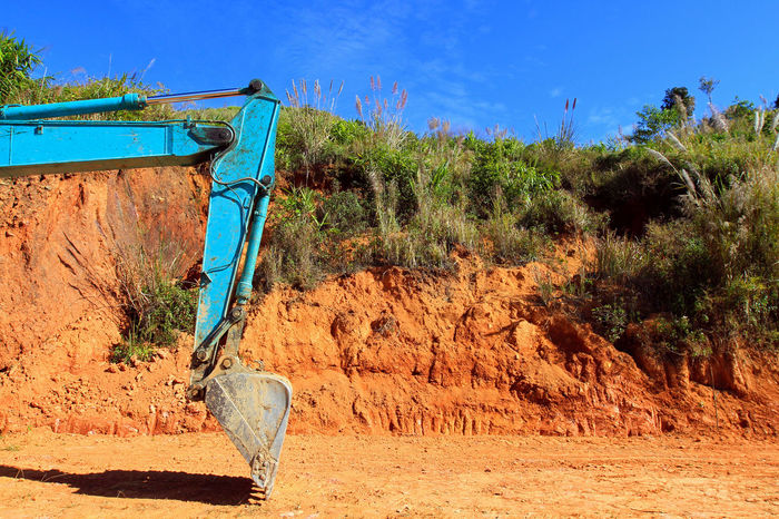 Green excavator digging the ground on construction site with blank copy space on right Construction Excavator Machine Machinery Blackhole Building Exterior Clear Sky Construction Industry Digger Excavation Ground Loader Backhoe No People Outdoors Site