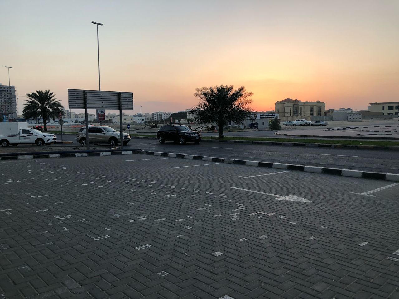 city, car, mode of transportation, motor vehicle, transportation, land vehicle, street, sky, architecture, sunset, building exterior, built structure, tree, tropical climate, nature, plant, road, no people, orange color, palm tree, outdoors, paving stone