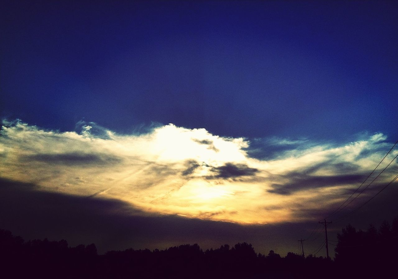 View Of Blue Sky At Dusk With Yellow Sun Reflection In Cloud