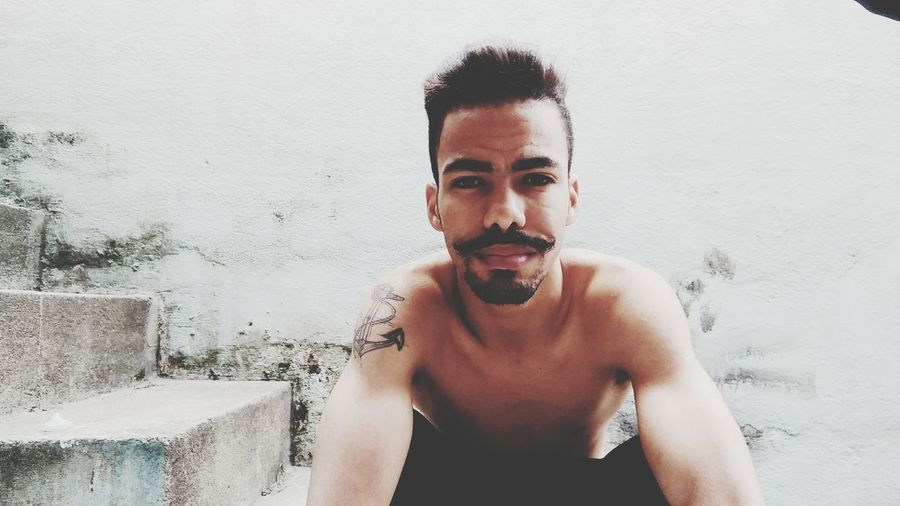 Portrait of shirtless young man crouching against wall
