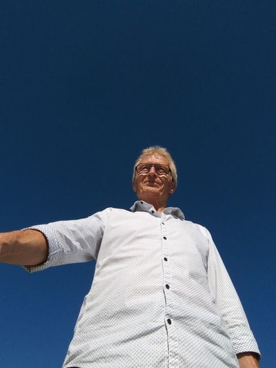 Low angle view of smiling senior man standing against clear blue sky during sunny day