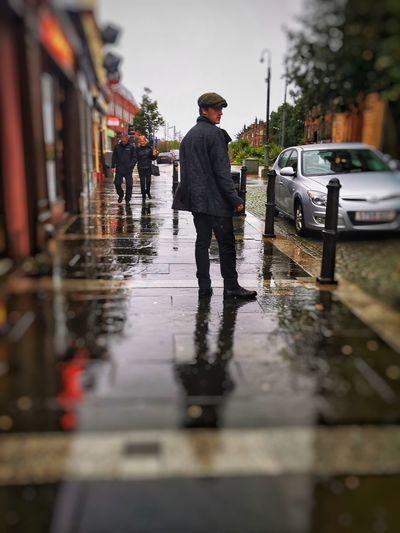 Man walking on wet street during rainy season