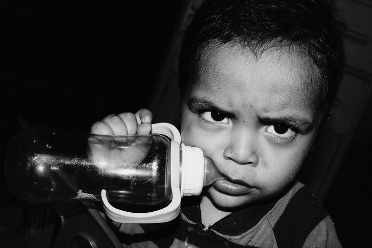Close-up portrait of boy with milk bottle against black background