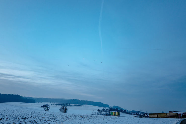 Scenic View Of Snowy Field Against Sky During Sunset