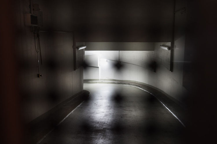 Way Down to a closed parking garage at night Architecture Indoors  No People Illuminated Built Structure Direction The Way Forward Transportation Absence Empty Entrance Parking Garage Dark darkness and light