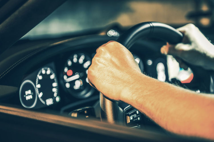 Close-up of hand holding steering wheel