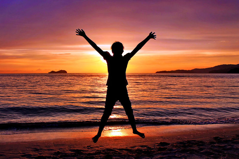 Girl With Arms Raised Jumping Against Sea During Sunset