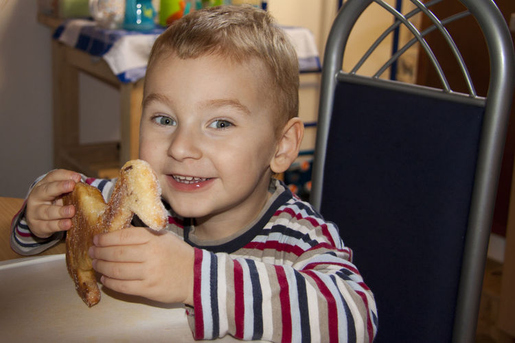 Portrait of cute boy eating cookie on table at home