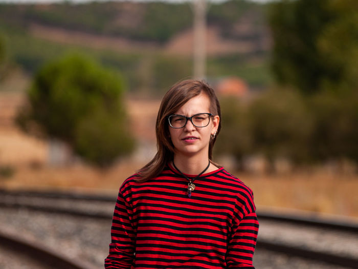 Portrait of smiling girl standing on railroad track