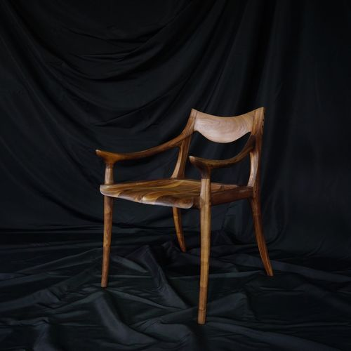 Empty wooden chair against black textile