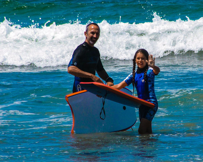 Portrait of father and daughter with surfboards in sea
