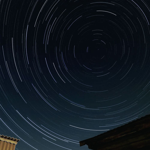 Low angle view of star trails against sky at night