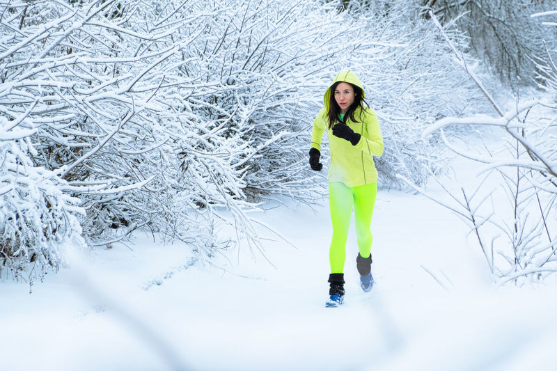 Full length portrait of woman on snow covered land