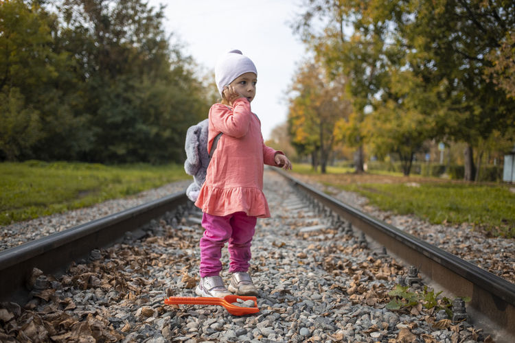 Girl standing on railroad track