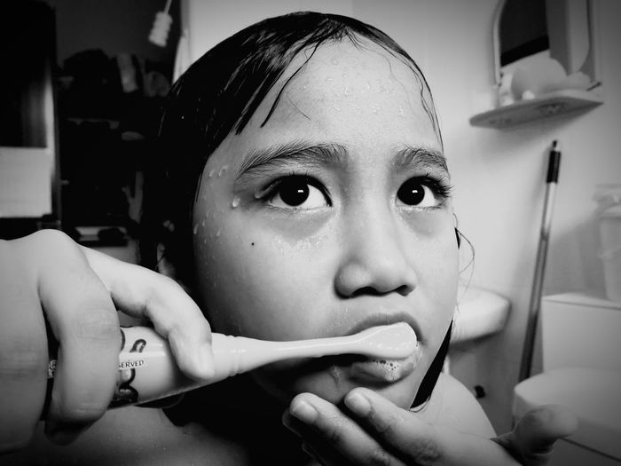 A little girl is brushing her teeth in black and white. EyeEm Selects Looking At Camera Headshot One Person Portrait One Woman Only Only Women Front View Close-up Adults Only One Young Woman Only Beauty People Indoors  Human Body Part Kid Brush Teeth Clean Little Girl Child Women Food Day The Week On EyeEm