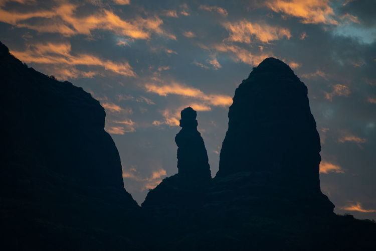 Low angle view of silhouette rocks against sky during sunset