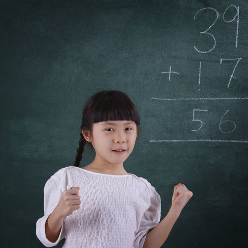 Girl Smiling While Learning Mathematics On Blackboard