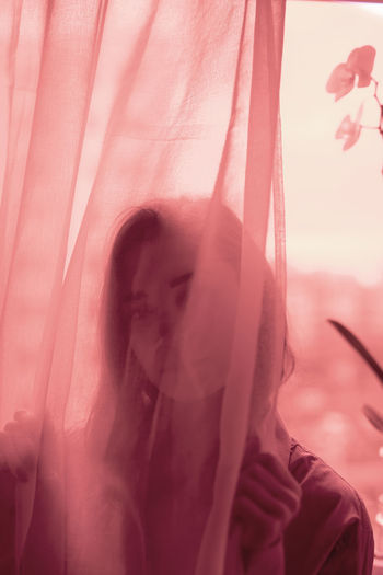 Portrait of woman against pink curtain