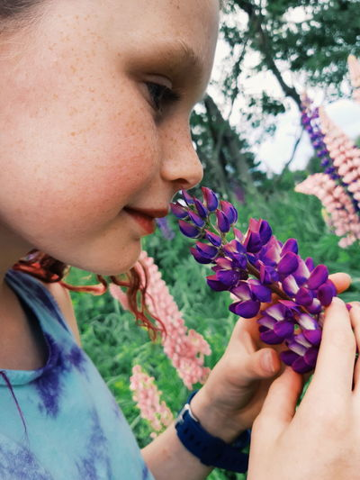 Close-up of woman hand holding purple flower