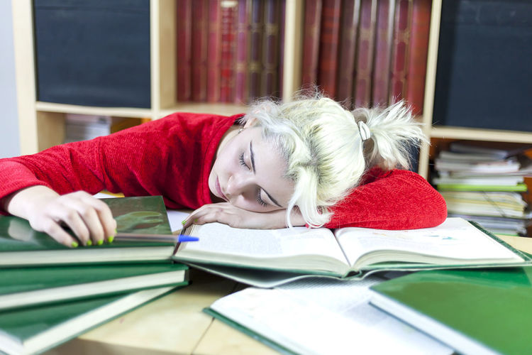 Young woman sleeping on desk while studying in library
