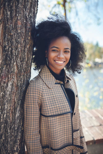 Beautiful african american young woman with afro and large hoop earrings in a stylish coat outdoors