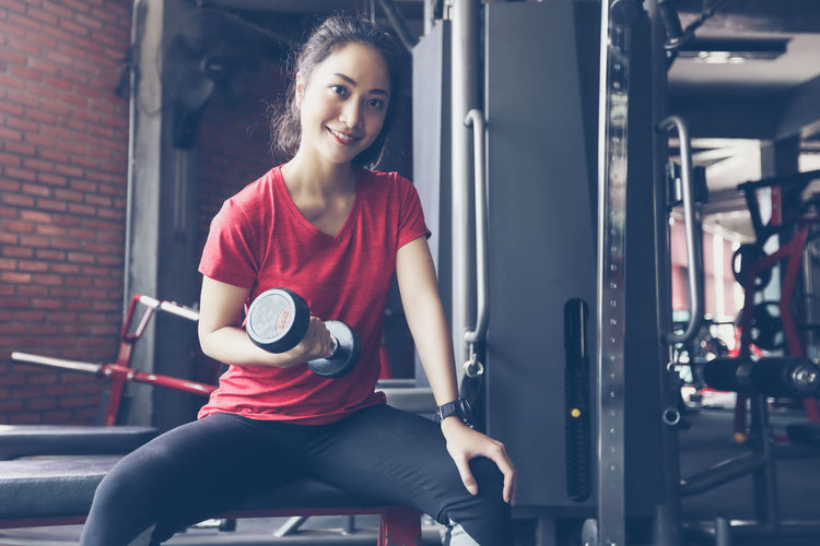 Portrait Of Smiling Young Woman Lifting Dumbbell At Gym